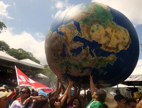 People transport a globe in a parade held during the World Social Forum in Belem, in Para, in the heart of the Brazilian Amazon, on January 28, 2009. Thousands of people are gathering in Belem for the six-day World Social Forum that aims to provide a leftist counterweight to the World Economic Forum in Davos, Switzerland, and which has grown to become the biggest anti-globalization event on the planet since the first time it was held in 2001.  AFP PHOTO/VANDERLEI ALMEIDA (Photo credit should read VANDERLEI ALMEIDA/AFP/Getty Images)